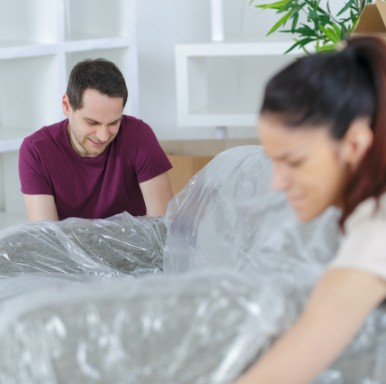 2 people moving sofa covered in plastic furniture wrap